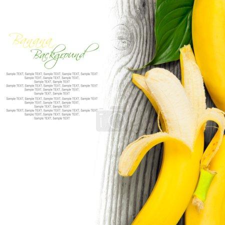 Foto de Foto de bananas peladas en tablero de madera con espacio en blanco - Imagen libre de derechos