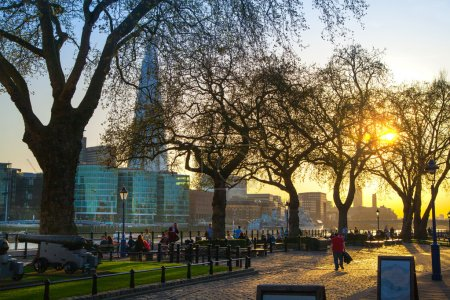 LONDON, UK - APRIL15, 2015: Tower park in sun set. River Thames side walk with people resting by the water