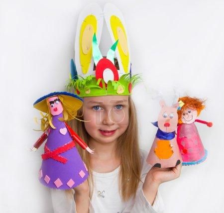 Little girl demonstrating her craft works Easter bonnet, paper dolls and reindeer