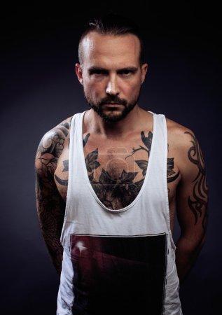 Foto de Un hombre con el tatuaje en sus brazos. Silueta de cuerpo musculoso. chico caucásico brutal hipster con corte de pelo moderno, buscando como cerrar Penal - Imagen libre de derechos