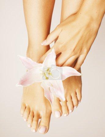 Photo pour Womans manucure pédicure avec lily fleur gros plan isolé sur salon de spa mains blanc parfait état - image libre de droit