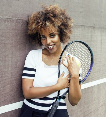 young stylish mulatto afro-american girl playing tennis, sport healthy lifestyle people concept