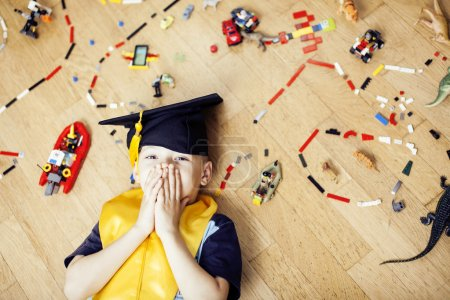 Photo for Little cute preschooler boy among toys lego at home in graduate hat smiling posing emotional, lifestyle people concept - Royalty Free Image