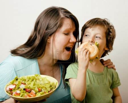 Fat woman holding salad and little cute boy with hamburger teasing