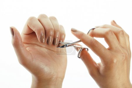 woman hands making no qualified manicure to herself isolated