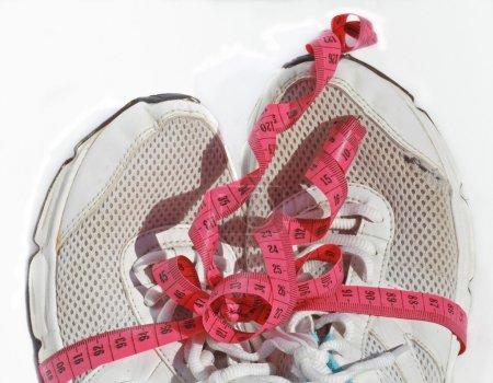 Photo pour Chaussures d'entraînement pour aînés minables avec ruban à mesurer comme un cadeau, beaucoup d'entraînement fait. gros plan isolé - image libre de droit