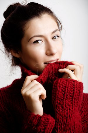 young pretty woman in sweater and scarf all over her face