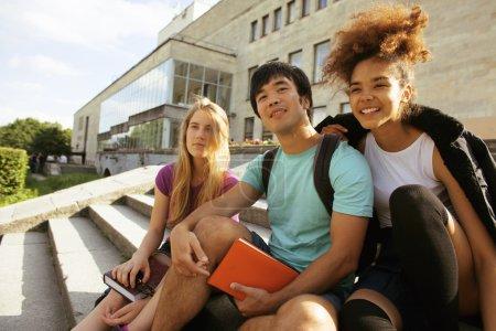 Photo pour Groupe mignon d'adolescents à la construction de l'université avec des livres câlins, souriant, retour à l'école - image libre de droit
