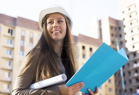 young pretty manager in hardhat at construction outside