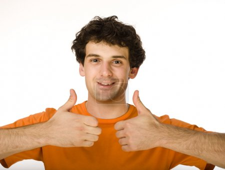 Portrait of happy young man giving thumbs up over white background