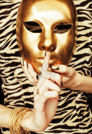 woman hands holding golden carnival mask, rich luxury manicure and jewelry