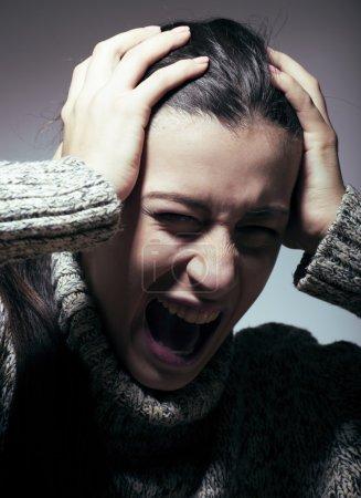 jeune jolie femme en difficulté, hurlant de douleur se bouchent