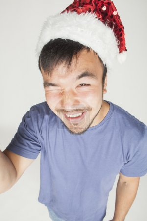 funy exotical asian Santa claus in new years red hat smiling