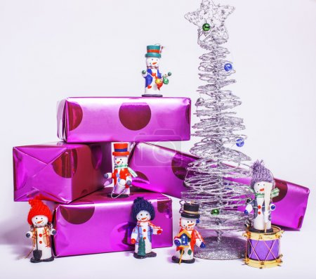 little sweet stylish snowmen toys with purple gifts and silver tree, isolated on white