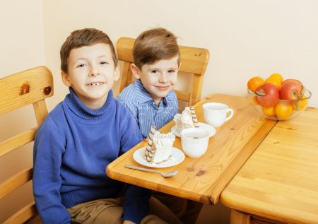 little cute boys eating dessert on wooden kitchen. home interior