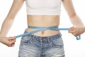 Girls stomach measuring with tape twice isolated close up on white