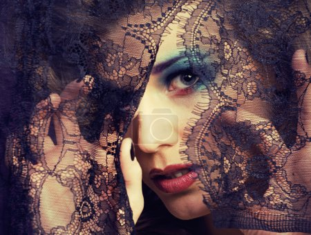 portrait of beauty young woman through lace close up mistery makeup