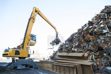 Large tracked excavator working a steel pile at a metal recycle