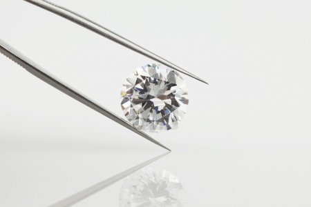 Photo for Large loose diamond photographed in diamond tweezers. Close up photograph of a natural polished diamond featuring reflection with a pale grey background. A perfect photograph to illustrate diamond information. - Royalty Free Image