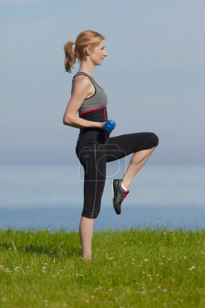 Photo for Young woman exercising in the morning by the sea - Royalty Free Image