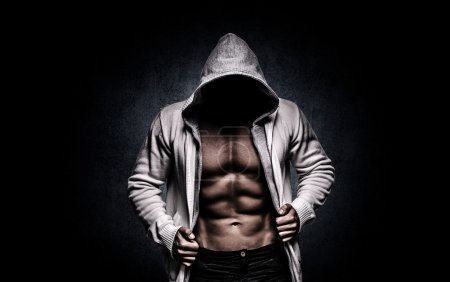 Photo pour A man in a hoodie, strong, sexy, on a dark background, in studio - image libre de droit