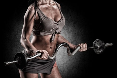 Brutal athletic woman pumping up muscles with barbell