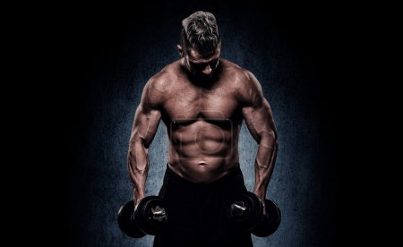 Cropped image of young muscular man doing heavy dumbbell exercis