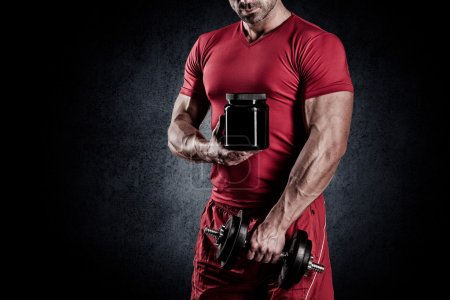 Photo for Young handsome muscular man with a sports nutrition and dumbbells in the hands of - Royalty Free Image