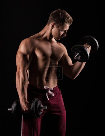 Handsome power athletic man with dumbbell confidently looking fo