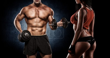 Photo for Athletic man and woman with a dumbbells - Royalty Free Image