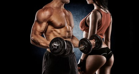 Photo for Fitness couple - woman and man with dumbbells in gym - Royalty Free Image