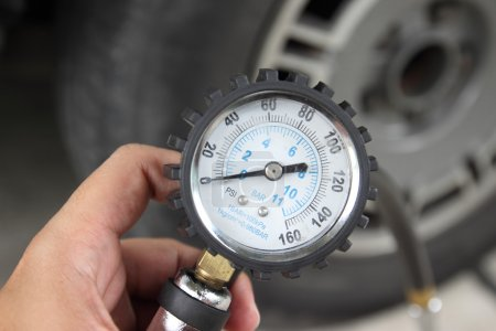Photo for Detail view of Hand holding pressure gauge for car tyre pressure measurement - Royalty Free Image
