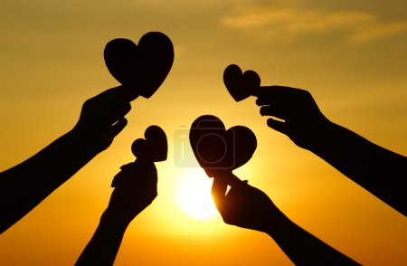 Photo pour Hands holding hearts silhouette against sunset - image libre de droit