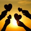Hands holding hearts silhouette against sunset...