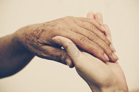 Photo pour Jeunes mains féminines touchant la vieille main féminine - prendre soin du concept des personnes âgées - image libre de droit
