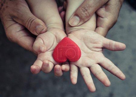 Photo pour De vieilles mains tenant la jeune main d'un bébé au cœur rouge - image libre de droit