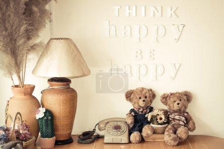 Photo pour Coin heureux d'une maison avec décoration de mots disant heureux de penser être heureux, ours, poupées, vieux téléphone, vase, pot, feu, plante, plume d'oiseau, panier - image libre de droit