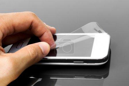 Photo pour Pose manuelle d'un film protecteur contre les rayures sur un smartphone - image libre de droit