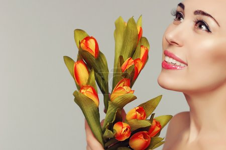 Spring beauty model studio shooting. Portrait of smiling woman with flowers orange yellow tulips on white background. Fashion fresh makeup. Sensual lips. Perfect skin. Tenderness. Romantic style.