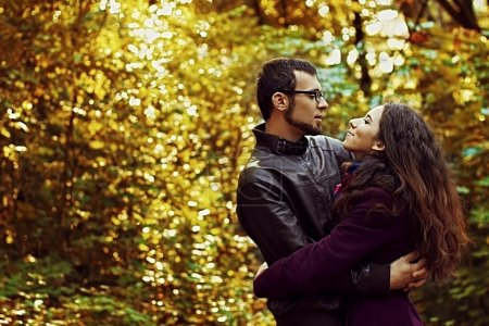 Young amorous couple handsome man and beautiful woman hugging each other in autumn park. Date. Amorousness. Romance.
