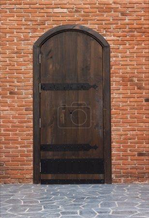 Old wooden door with red brick walls.