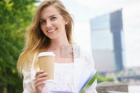 Photo for Young business Woman with coffee to Go and green notebook. - Royalty Free Image