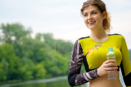 Athletic smiling woman with bottle of water