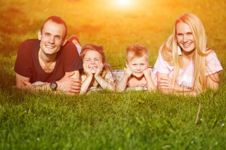 Foto de Familia jugando en el parque en el césped. efecto de destello de lente - Imagen libre de derechos