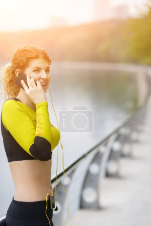 Photo for Happy sporty girl talking on phone in park. Image with lensflare - Royalty Free Image