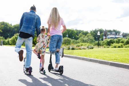 Photo for Family and children with scooters in the park - Royalty Free Image