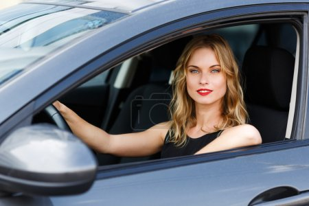Beautiful caucasian young blond woman sitting behind wheel of car