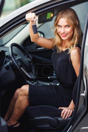 Photo pour Élégante jeune femme blonde assise derrière le volant et tenant des clés de voiture - image libre de droit