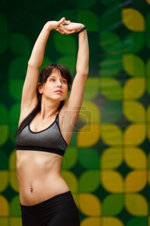 Brunette young woman preparing for training in gym