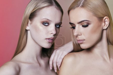 Portrait of two woman with blond hair made in studio.